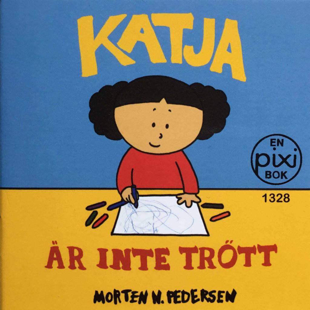 Omslag, Katja är inte trött, Katja smiler og tegner med fargestifter på ett ark